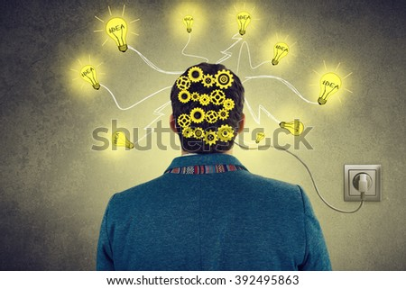 Idea concept.Businessman with new idea turned to camera with a  bright light bulbs.Rear back view of student man standing in front of a wall with bulbs connected to outlet. - stock photo
