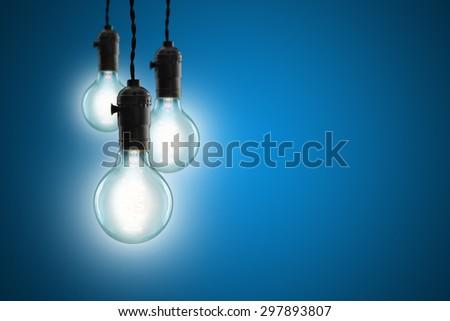 Idea concept -  incandescent bulb on blue background - stock photo