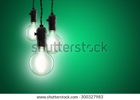 Idea concept -  incandescent bulb on green background - stock photo