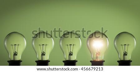 Idea concept. Light bulbs on green background - stock photo