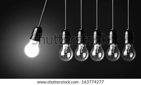 Idea concept on black. Perpetual motion with light bulbs - stock photo