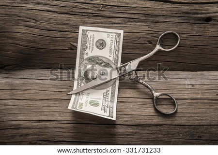 Idea, concept, symbol of budget cut. Business concept. Whole 100 Dollars are cutting with scissors on old retro vintage aged wooden  background. Empty copy space for inscription or object.  - stock photo