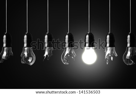 idea concept with broken bulbs and one glowing bulb - stock photo