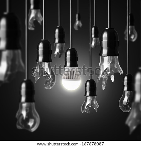 idea concept with broken bulbs and one glowing LED bulb - stock photo