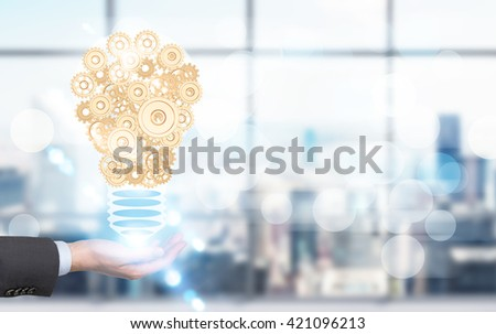 Idea concept with businessman hand holding abstract lightbulb made of golden gears on blurry office background - stock photo