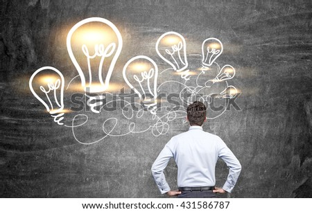 Idea concept with businessman looking at illuminated lightbulb sketches on chalkboard background - stock photo
