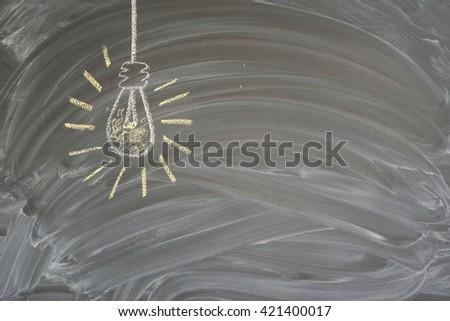 idea concept with glowing light bulb on blackboard - stock photo