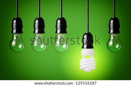Idea concept with light bulbs and energy save bulb. Green background. - stock photo