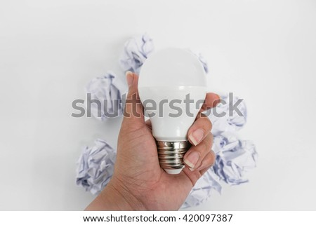 Idea icon as a LED bulb in hand with crumble paper - stock photo