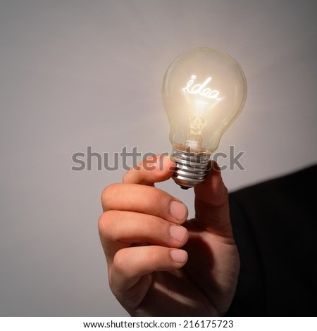 idea lamp bulb holded by business man hand - stock photo