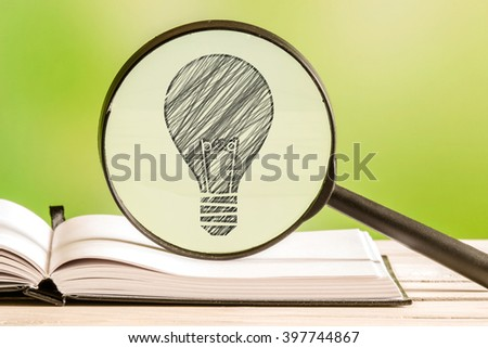 Idea search with a pencil drawing of a light bulb in a magnifying glass - stock photo