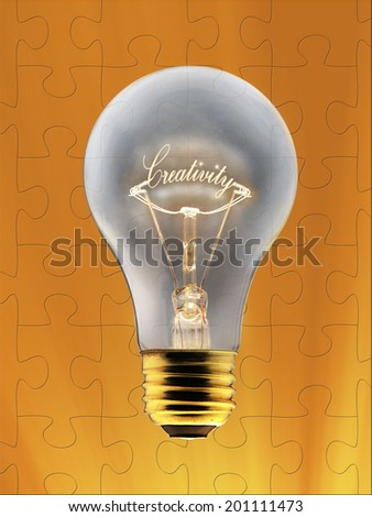 Idea symbol, light bulb and jigsaw puzzle. - stock photo