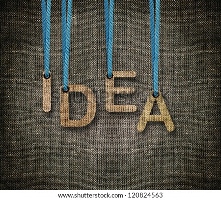 Idea word hanging by rope as puppeteer on sackcloth background. - stock photo