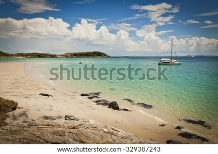 Ideal beach on Keppel Island, Queensland, Australia. Sun soaked sand beside turquoise ocean at the start of the Great Barrier Reef. - stock photo