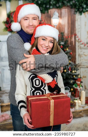 Ideal Christmas. Young and beautiful couple is standing in festive New Year living room just before the Christmas. Pair is hugging and looking directly in the camera - stock photo