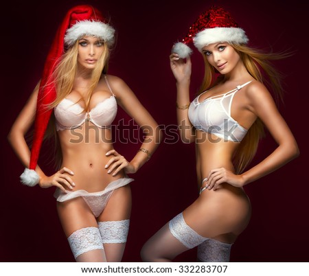Ideal sexy blonde girls posing in lingerie and santa claus hat. Studio shot. Christmas content. - stock photo