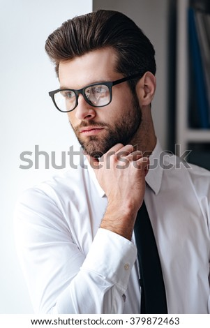 Ideas in his head. Handsome young businessman in glasses looking away and keeping hand on chin while standing in office  - stock photo