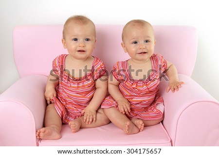 Identical ten month old twin baby girls seated on a pink child size sofa. - stock photo