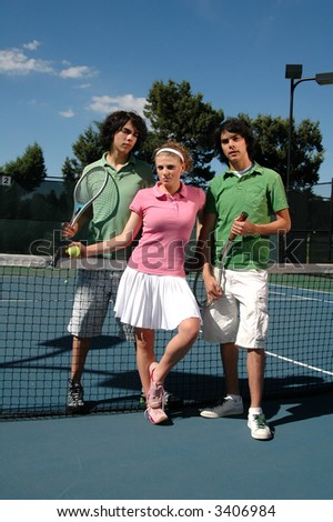Identical twin brothers and a girl hanging out on the tennis courts - stock photo
