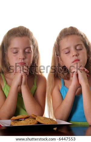 Identical twin girls saying grace - stock photo