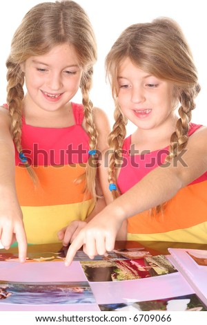 identical twin sisters putting photo's in an album - stock photo