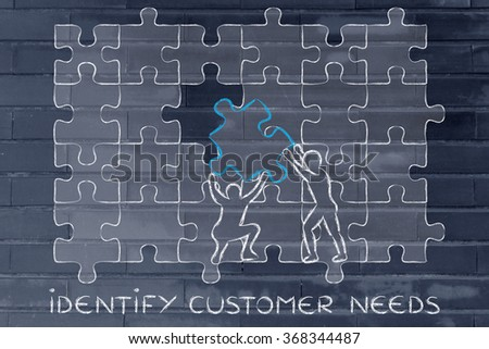 identify customer needs: men completing a jigsaw puzzle with the missing piece - stock photo