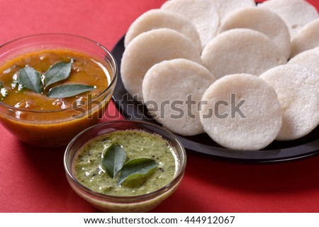 Idli with Sambar and coconut chutney on red background, Indian Dish : south Indian favourite food rava idli or semolina idly or rava idly, served with sambar and green chutney. - stock photo