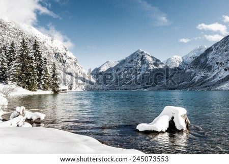 idyllic cold lake at snow mountain landscape in winter scenery - stock photo