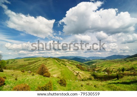 Idyllic countryside view. Green fields on the hills. - stock photo