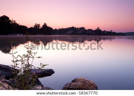 idyllic countryside view with lake and houses during sunrise - stock photo