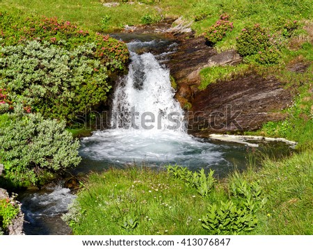 Idyllic place in the mountains with a waterfall and a small lake and blooming alpine roses - stock photo