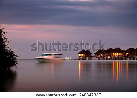 idyllic purple sunset with resort in Maldives - stock photo