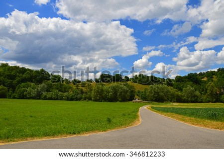 Idyllic rural landscape of a country road, that leads towards green pasture, hills with trees and a beautiful cloudscape. - stock photo