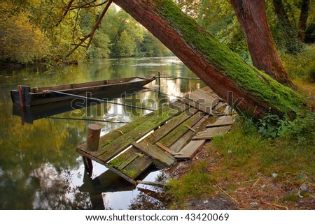 idyllic scene of lonely boat, river and forest - stock photo