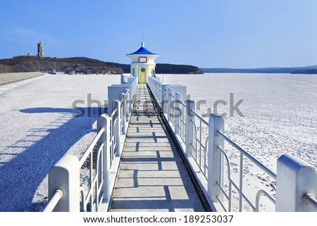 idyllic scenery with a pier in a frozen lake - stock photo
