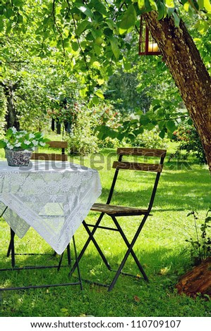 Idyllic setting of a small coffee table and a wooden chair under an apple tree in green summer garden - stock photo