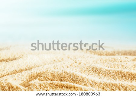 Idyllic tropical beach background with the golden sand rippled by the wind and tide under a hot summer sun for that perfect summer getaway and vacation - stock photo