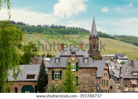 idyllic village Lieser, beside mosel river at springtime, with hillside vineyards - stock photo