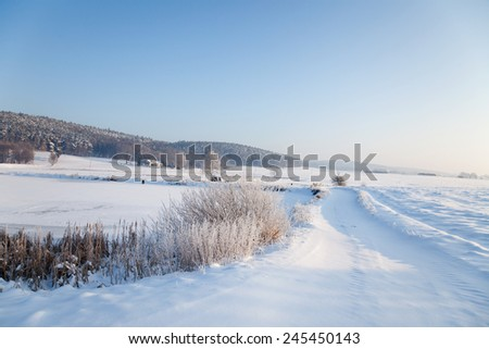 idyllic winter landscape in Thuringia with a frozen pond - stock photo