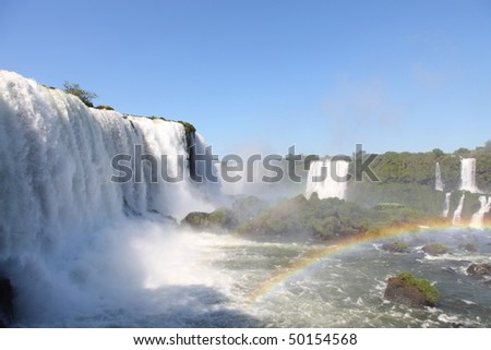 Iguassu waterfalls with rainbow on a sunny day early in the morning. The biggest waterfalls on earth. - stock photo