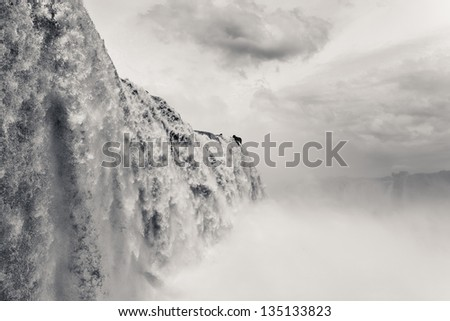 Iguazu falls, one of the new seven wonders of nature. UNESCO World Heritage site. View from the brazilian side during rains season. Black and white. - stock photo