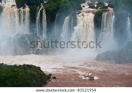 Iguazzu (Iguassu) Falls.  Tourists enjoy a close-up view of the falls by boat. The famous South American waterfall borders Argentina and Brazil and has been designated a National Park. - stock photo