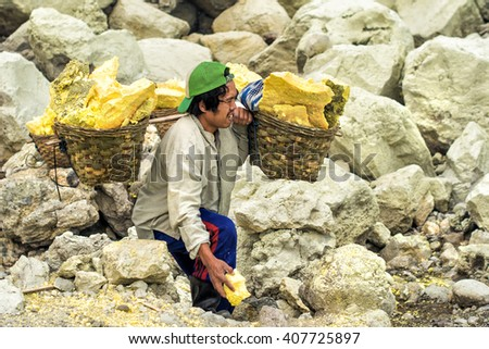 Ijen Crater, Indonesia - May 25: Sulfur miner carrying baskets with sulfur at Kawah Ijen volcano in East Java, Indonesia.  - stock photo