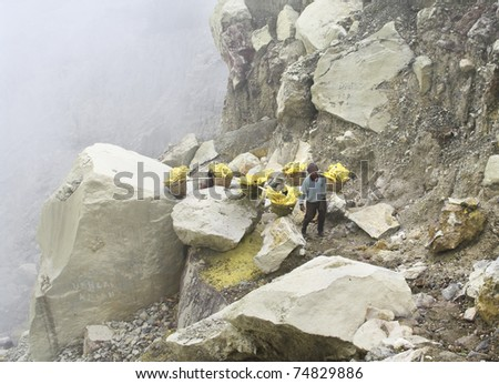 IJEN VOLCANO, INDONESIA - JAN 10: Worker carrying sulfur inside Ijen crater on January 10, 2011 in Ijen Volcano, Indonesia. He carries the load of around 90kg to the top of the rip and then 3 km down. - stock photo