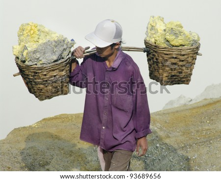 IJEN VOLCANO, INDONESIA - JAN 10: Worker carrying sulfur inside Ijen crater on January 10, 2011 in Ijen Volcano, Indonesia. He carries the load of around 60kg to the top of the rip and then 3km down. - stock photo