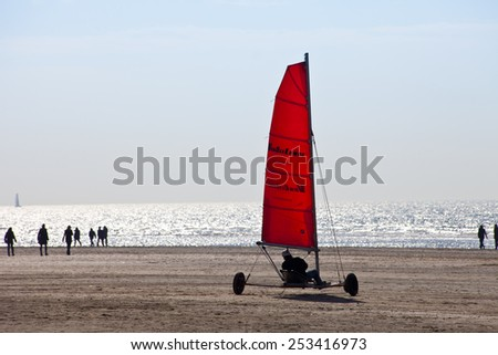 IJMUIDEN, THE NETHERLANDS -MARCH 20TH 2011: Beach sailing cart (Blokart) with red sail on the beach in IJmuiden on March 20th 2011  - stock photo