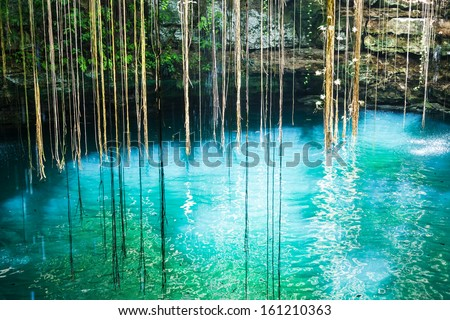 Ik-Kil Cenote near Chichen Itza, Mexico. Lovely cenote with transparent turquoise waters and hanging roots - stock photo