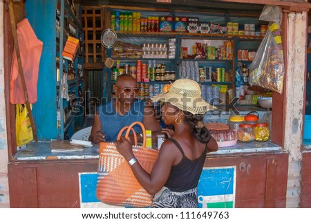 ILAKAKA, MADAGASCAR - JAN, 27: An unidentified woman buying in a typical grocery shop on Jan 27, 2004 in Ilakaka. Ilakaka is the sapphire city in southern Madagascar - stock photo