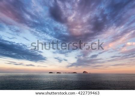 Ilhas Cagarras Islands in the Horizon of the Ocean by Sunset, Rio de Janeiro, Brazil - stock photo