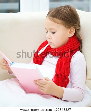 Ill little girl is sitting on sofa with thermometer in her mouth and reading book - stock photo